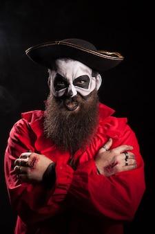 Malvado pirata barbudo con maquillaje espeluznante para halloween sobre fondo negro.