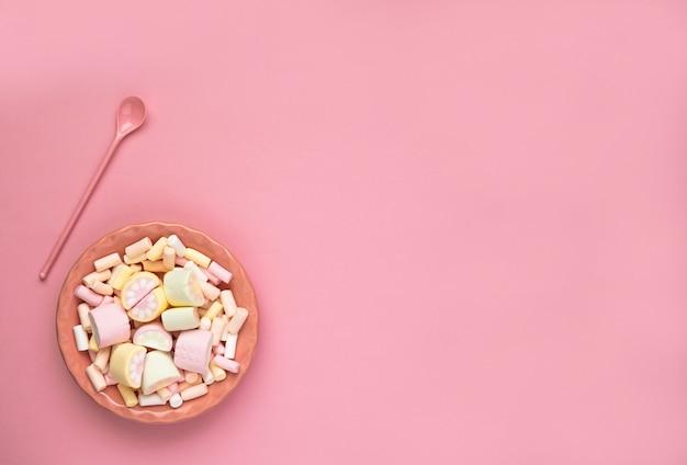 Malvaviscos de colores en un plato rosa aislado sobre un fondo rosa. primer plano de textura de malvavisco esponjoso.