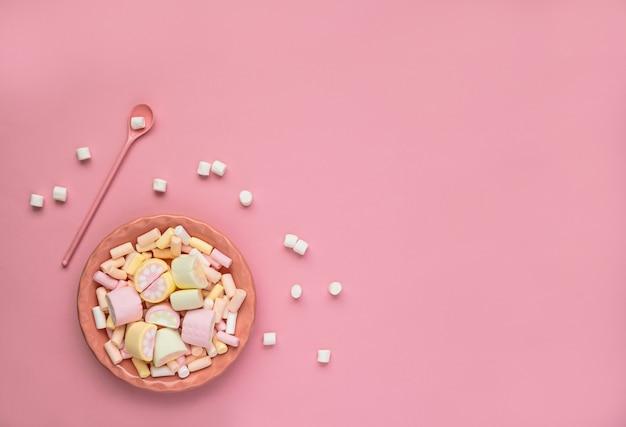 Malvaviscos coloridos en un plato rosa aislado sobre un fondo rosa. malvaviscos dispersos primer plano de textura de malvavisco esponjoso. endecha plana