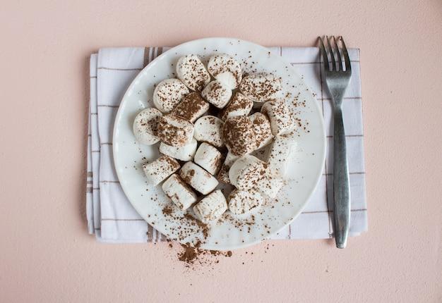 Malvaviscos espolvoreados con cacao en un plato blanco con un tenedor sobre una toalla. comida dulce vista superior