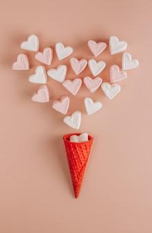 Malvaviscos en forma de corazón rosa y blanco con cono de galleta sobre fondo rosa. vista superior. copia espacio