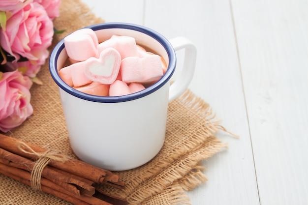 Malvaviscos en forma de corazón en una taza de chocolate caliente. el amor y el concepto del día de san valentín.