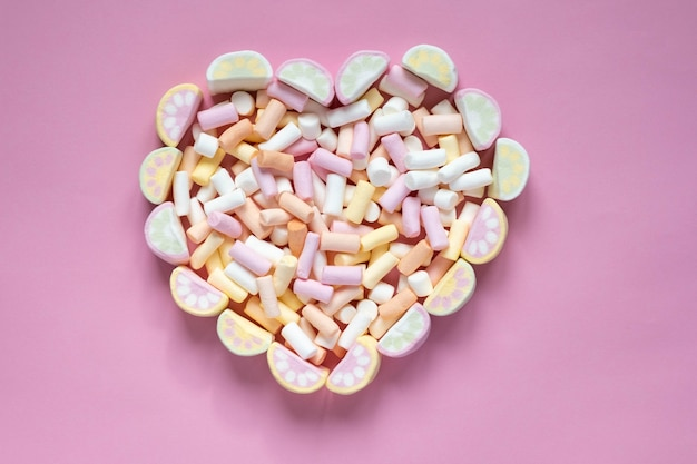 Malvaviscos multicolores en forma de corazón sobre un fondo rosa. vista desde arriba