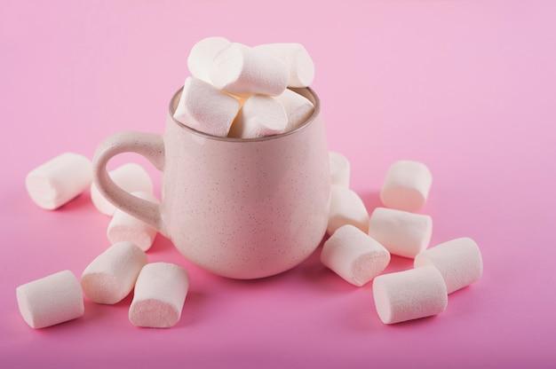 Malvaviscos en una taza en un espacio rosa de cerca y copie el espacio. vista superior de malvavisco en cacao o chocolate caliente en un espacio rosa.