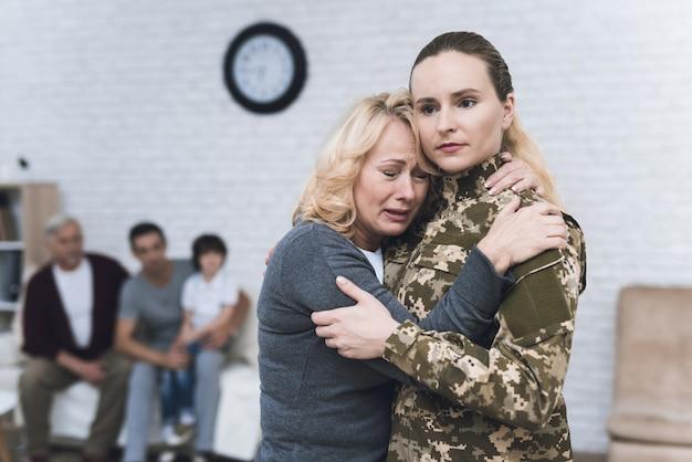 Mamá abraza a la hija que va a la guerra con su casa.