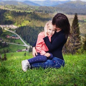 Mamá abraza a una pequeña hija en la cima de la montaña.