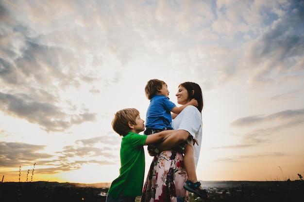 Mamá abraza con sus dos pequeños hijos tiernos de pie en los rayos.