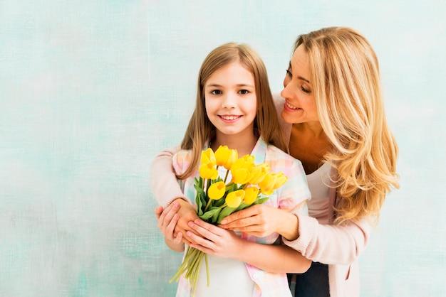 Mamá abrazando a hija con tulipanes y mirando a niña
