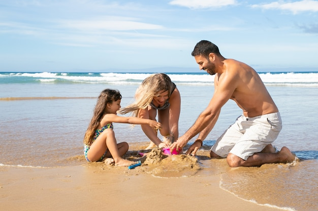 Mamá alegre, papá e hija disfrutando juntos de vacaciones en el mar, jugando con sus hijas juguetes de arena, construyendo castillos de arena