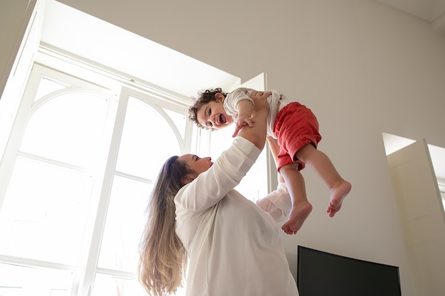 Mamá alegre sosteniendo al bebé emocionado en brazos, levantando las manos en el aire. ángulo bajo. niño en casa y concepto de infancia.