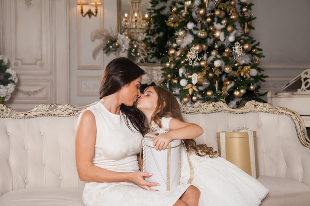 Mamá alegre y su linda hija intercambiando regalos en el interior clásico blanco con el telón de fondo de un piano y un árbol de navidad decorado.
