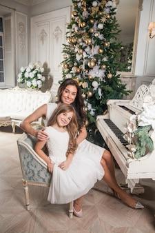 Mamá alegre y su linda hija niña en interior clásico blanco jugando en un piano blanco con el telón de fondo de un árbol de navidad decorado. año nuevo 2021.