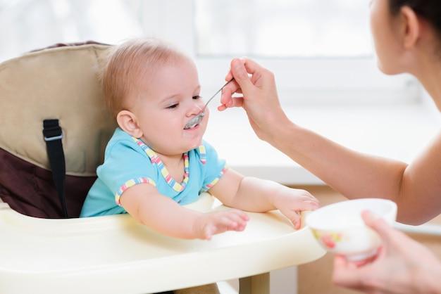 Mamá alimenta a su bebé de nueve meses en casa