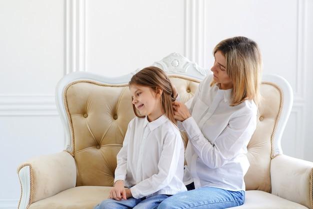 Mamá alisa el cabello de su hija