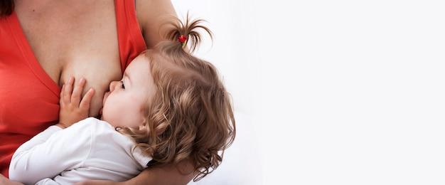 Mamá está amamantando al bebé. copie el espacio. bandera