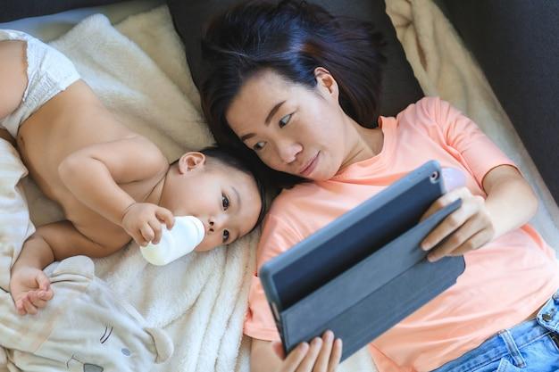 Mamá asiática viendo y jugando con tableta digital con su lindo bebé