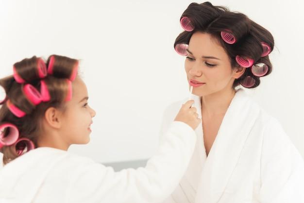 Mamá ayuda a la niña a maquillarse y verse hermosa.