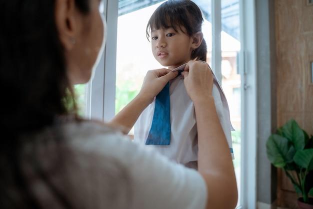 Mamá ayuda a ponerse el uniforme de su hija antes de la escuela