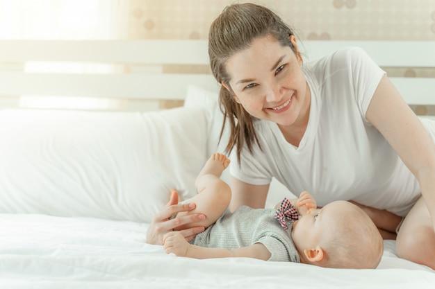 Mamá y bebé felizmente se burlan mutuamente en una cama blanca.