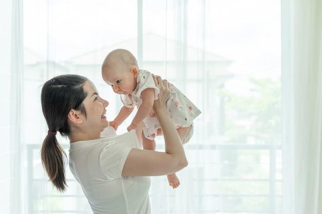 Mamá y bebé felizmente se burlan mutuamente