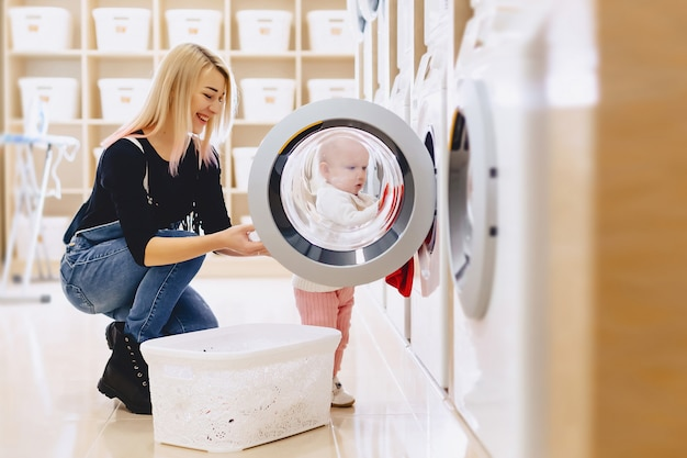 Mamá y bebé en la lavandería toman cosas y juegan.