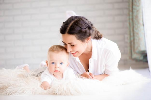 Mamá y bebé en el pañal que juegan en dormitorio soleado.