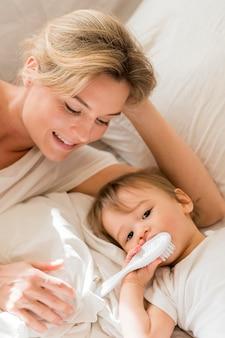 Mamá y bebé sentado en la cama