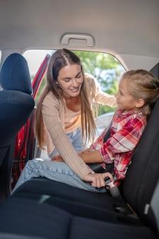 Mamá cariñosa abrochando el cinturón de seguridad de su hija en el asiento trasero del coche