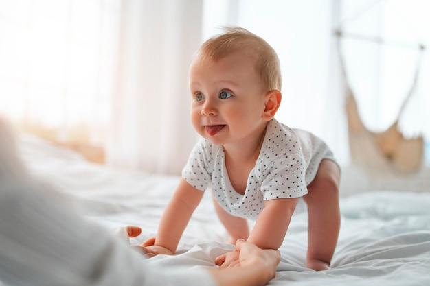 Mamá cariñosa con su bebé recién nacido en casa. madre e hijo en una cama blanca. mamá y bebé en pañales jugando en dormitorio soleado. padre e hijo pequeño relajándose en casa. familia divirtiéndose juntos.