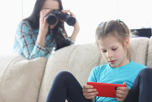 Mamá controla a su hija con el teléfono a través de binoculares