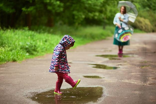 Mamá se para detrás con paraguas mientras su hija juega en piscinas después de la lluvia