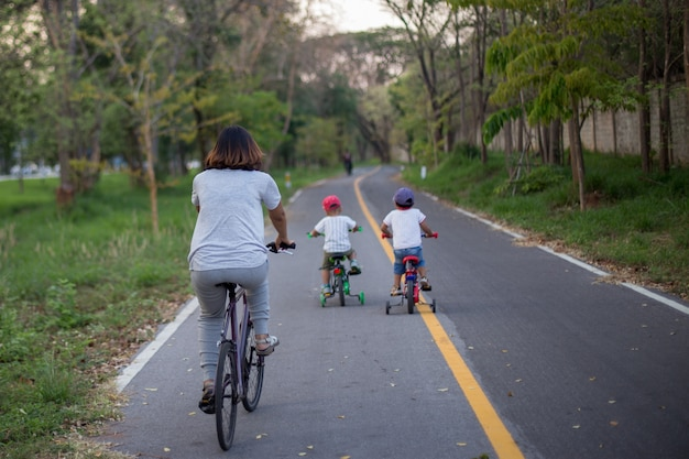 Mamá y dos hijos andan en bicicleta en el carril bici.