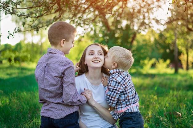 Mamá con dos hijos en el parque. el niño está besando a su madre. feliz maternidad
