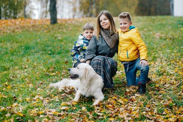 Mamá con dos hijos y un perro están caminando en el parque en otoño