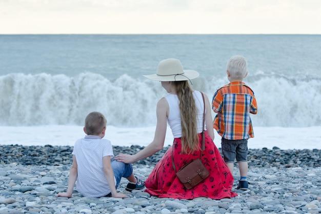 Mamá y dos hijos sentados en la playa y mirando las olas. vista trasera