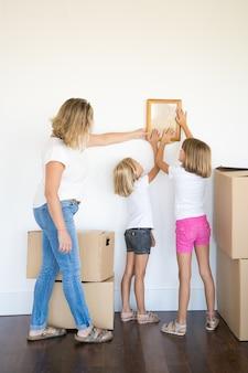 Mamá y dos niñas colgando marco de fotos en blanco en la pared blanca