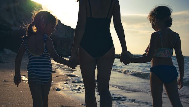 Mamá y dos pequeñas hijas caminan por la orilla del mar en traje de baño, tomados de la mano. vee desde atrás.