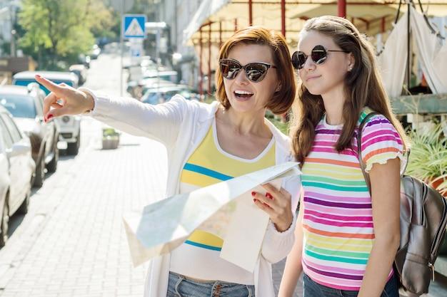 Mamá e hija adolescente turista mirando el mapa