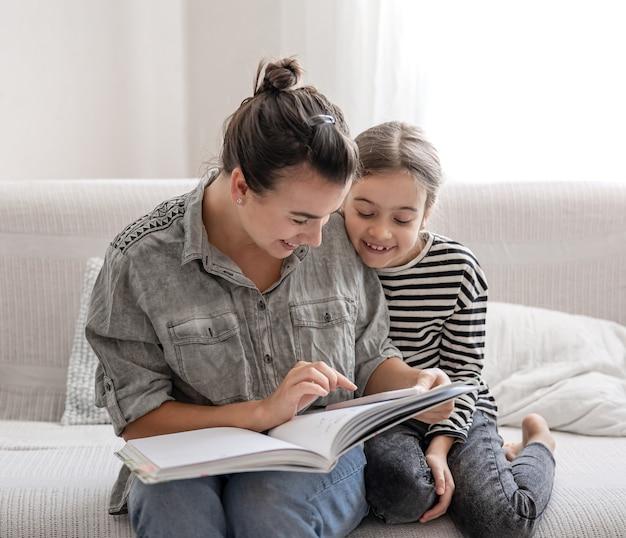 Mamá e hija alegres están descansando en casa, leyendo un libro juntos