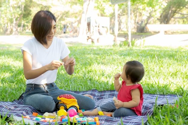 Mamá e hija asiáticas jovenes hermosas que juegan los bloques del juguete para aprender el desarrollo feliz
