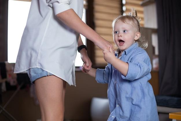 Mamá e hija bailan en casa.