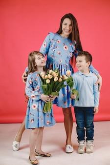 Mamá e hija con cabello largo. niños vestidos de azul. mamá con tulipanes.