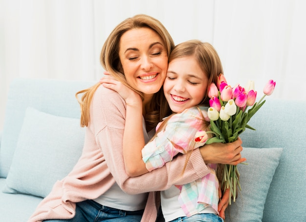 Mamá e hija con la cara satisfecha abrazándose