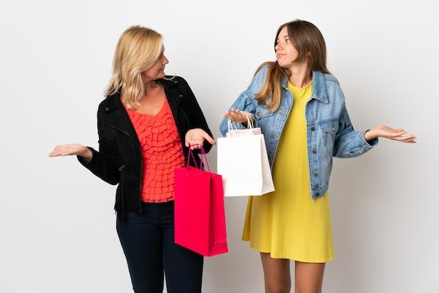 Mamá e hija comprando algo de ropa aislado en la pared blanca haciendo un gesto sin importancia mientras levanta los hombros