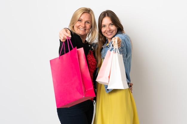 Mamá e hija comprando algo de ropa aislado en la pared blanca