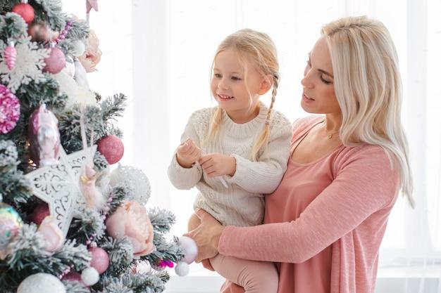Mamá e hija decoran el árbol rosado de navidad en el interior.