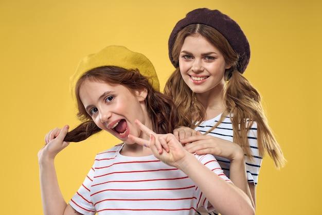 Mamá e hija divertidas con sombreros moda diversión alegría familia fondo amarillo