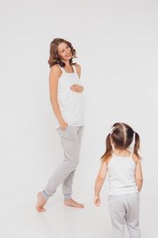Mamá e hija se divierten en un fondo blanco. la mujer embarazada y el niño juegan juntos.