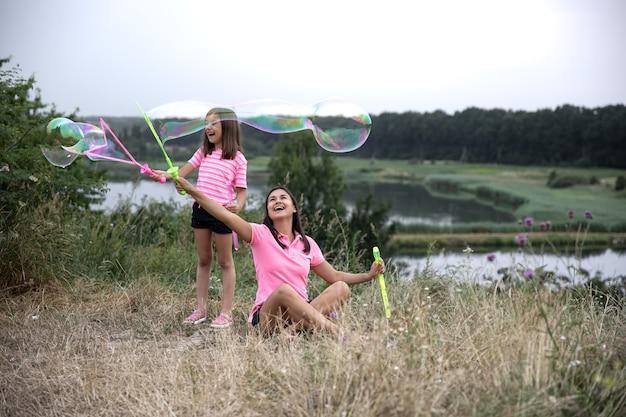 Mamá e hija se divierten juntas, hacen grandes pompas de jabón, recreación al aire libre.