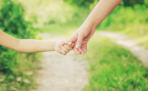 Mamá e hija están caminando por la carretera tomados de la mano.